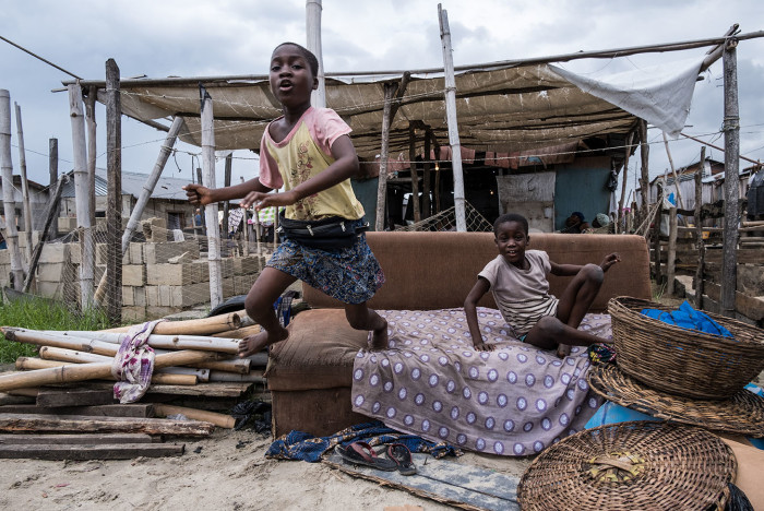 In the informal fishing community of Isale Ijebu in Ajah lagos, a child jumps from a sofa onto the sand