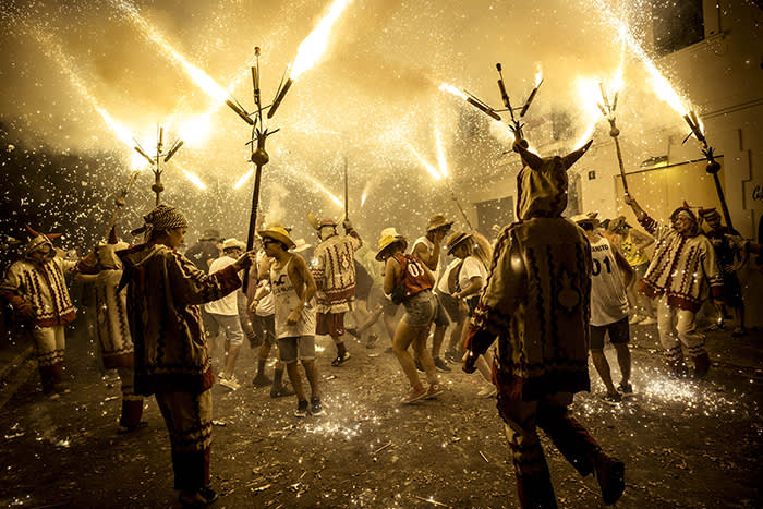 15 September 2018, Spain, Sitges: Spectators dance under the sparks from fireworks during 'Santa Tecla' Festival in Sitges, Spain, 15 Septemaber 2018. Photo: Matthias Oesterle/ZUMA Wire/dpa