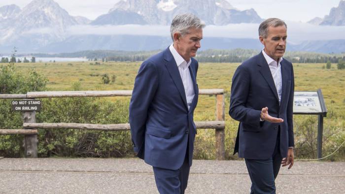 Jerome Powell, chairman of the U.S. Federal Reserve, left, and Mark Carney, governor of the Bank of England (BOE), walk the grounds during the Jackson Hole economic symposium, sponsored by the Federal Reserve Bank of Kansas City, in Moran, Wyoming, U.S., on Friday, Aug. 23, 2019. Powell said the U.S. economy is in a favorable place but faces