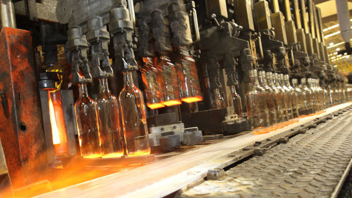 Glass bottles being moulded at Encirc Glass plant at Elton near Chester, who use co-bots to handle hot glassware.