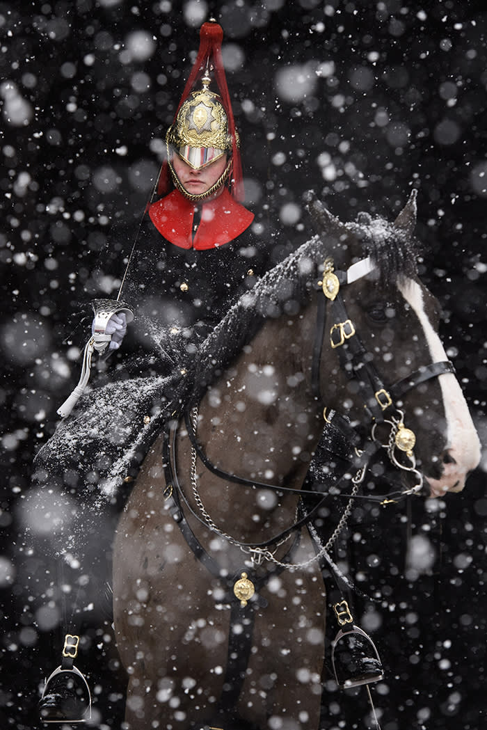 "LONDON, UNITED KINGDOM - FEBRUARY 28: A Household Cavalry Guard sits on horseback on duty as heavy snow hits Westminster on February 28, 2018 in London, United Kingdom. Freezing weather conditions dubbed the ""Beast from the East"" bring snow and sub-zero temperatures to the UK. Amber warnings are in place in northern England, the East Midlands, London, the east and south-east of England. Scotland's weather warning has been upgraded to red, which means risk to life, widespread damage, travel and power disruption are likely. (Photo by Leon Neal/Getty Images)"