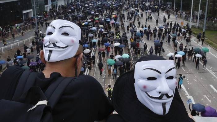 "Anti-government protesters wearing masks march past police headquarters in Hong Kong, Tuesday, Oct. 1, 2019. Thousands of black-clad pro-democracy protesters defied a police ban and marched in central Hong Kong on Tuesday, urging China's Communist Party to ""return power to the people"" as the party celebrated its 70th year of rule. (AP Photo/Gemunu Amarasinghe )"