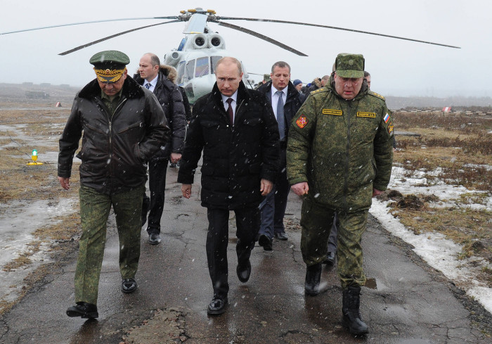 Russia's President Vladimir Putin (front C) and Defence Minister Sergei Shoigu (front L) walk to watch military exercises upon his arrival at the Kirillovsky firing ground in the Leningrad region, on March 3, 2014. Crimea, the strategic host to tsarist and Kremlin navies since the 18th century, has been under de facto occupation by Moscow-backed forces since Putin won recently parliament's authorisation to send troops into Ukraine. AFP PHOTO/ RIA-NOVOSTI/ POOL/ MIKHAIL KLIMENTYEV / AFP / RIA-NOVOSTI / MIKHAIL KLIMENTYEV (Photo credit should read MIKHAIL KLIMENTYEV/AFP/Getty Images)