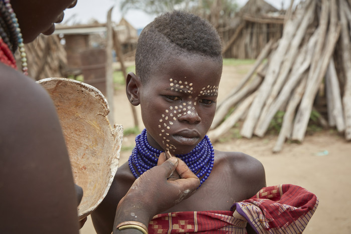 A youth has his face painted in Dus, Ethiopia, September 2017. A sustainable travel venture is working to build mutually beneficial exchanges between tourists and the local peoples in Ethiopia's Omo Valley, where dams are threatening to upend traditional tribal life. (Andy Haslam/The New York Times) Credit: New York Times / Redux / eyevine For further information please contact eyevine tel: +44 (0) 20 8709 8709 e-mail: info@eyevine.com www.eyevine.com