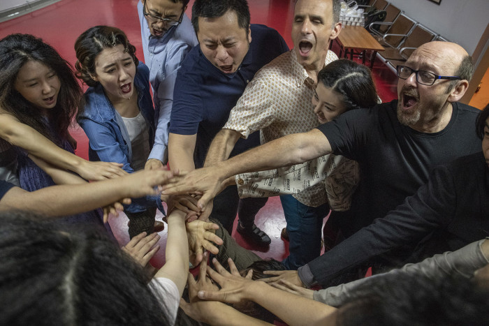Beijing August 15th, 2018 Actors, musician and director of a Chinese production of Shakespeare's The Tempest, put their hands together before the start of a performance at the National Centre for Performing Arts. Gilles SabriÈ for The Financial Times