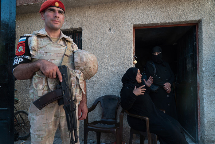 A member of the Russian military stands near a Syrian woman outside a house on August 13, 2018 in Yalda, in the southern suburbs of the capital Damascus, during a guided tour with the Russian army. - More than 350,000 people have been killed and millions displaced since Syria's war started with the brutal repression of anti-government protests in 2011. (Photo by Andrei BORODULIN / AFP) (Photo credit should read ANDREI BORODULIN/AFP/Getty Images)