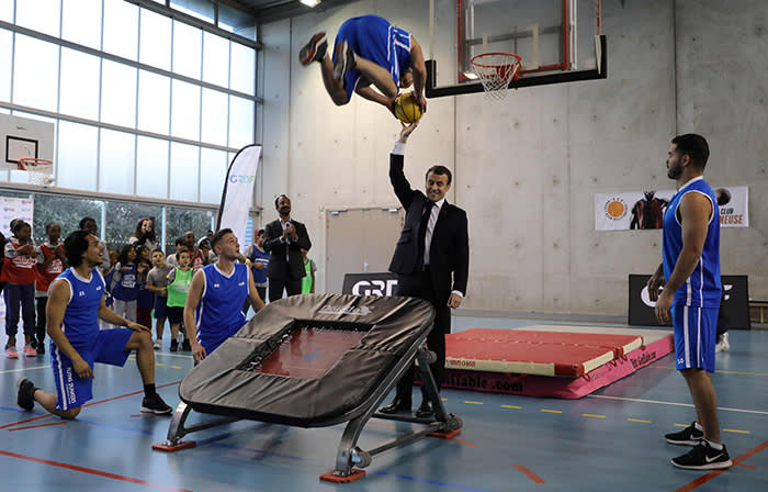 French President Emmanuel Macron (C) gestures as he takes part in display of basketball skills during a visit at the Jesse Owens gymnasium in Villetaneuse near Seine-Saint-Denis, north of Paris on February 27, 2018. / AFP PHOTO / LUDOVIC MARINLUDOVIC MARIN/AFP/Getty Images