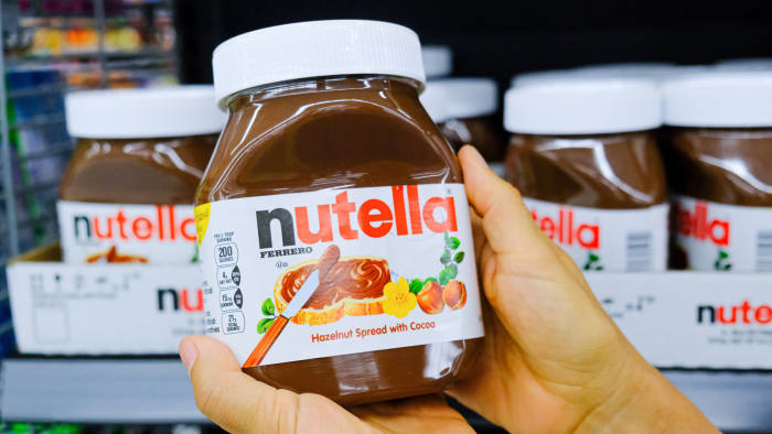 Shoppers hand holding a plastic jer of nutella brand hazelnuy spread with cocoa for sale  in a supermarket aisle