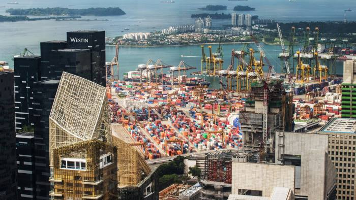 Containers sit among gantry cranes at Tanjong Pagar container terminal as Sentosa Island stands in the background in Singapore, on Friday, May 20, 2016. City Developments Ltd., Singapore's second-largest developer, may seek to buy offices this year as rising interest rates makes such assets cheaper worldwide. Photographer: Nicky Loh/Bloomberg