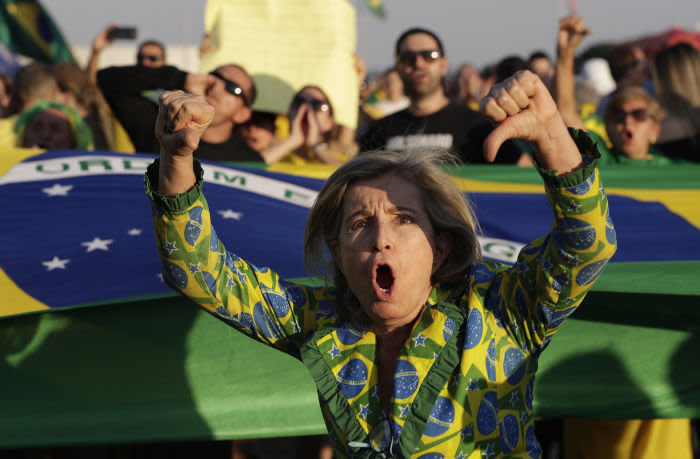 A supporter of Brazil's President Jair Bolsonaro shouts slogans and flashes thumbs down during a protest against the decision taken by the Supreme Court facilitating the release from jail of former President Lula Inacio Lula da Silva, in front at the National Congress building in Brasilia, Brazil, Saturday, Nov. 9, 2019. Da Silva addressed thousands of jubilant supporters outside a union headquarters on Saturday, a day after he was freed. (AP Photo/Eraldo Peres)