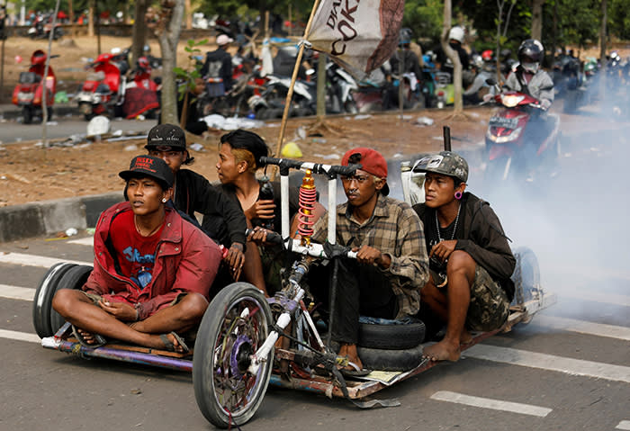 """Extreme Vespa enthusiasts drive their bike near the site of a weekend festival for extreme Vespas in Semarang, Central Java, Indonesia, July 22, 2018. REUTERS/Darren Whiteside SEARCH """"WHITESIDE VESPA"""" FOR THIS STORY. SEARCH """"WIDER IMAGE"""" FOR ALL STORIES. TPX IMAGES OF THE DAY."""