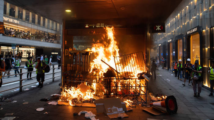 A barricade set on fire by demonstrators burns at an entrance to Central Station, operated by MTR Corp., during a protest in the Central district of Hong Kong, China, on Sunday, Sept. 8, 2019. Hong Kong police fired tear gas at protesters who built barricades, started blazes and paralyzed traffic in the city's prime business area on Sunday as unrest becomes increasingly difficult to contain. Photographer: Kyle Lam/Bloomberg
