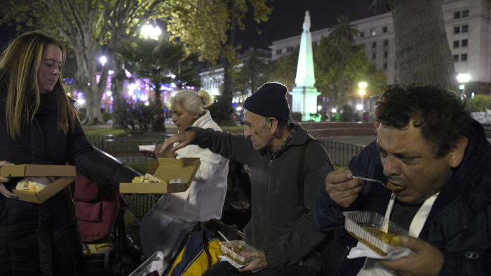 Poor and homeless people eat a lentil stew while a Red Solidaria (Solidarity Network) volunteer offers bread at Plaza de Mayo square, in front of the Casa Rosada government palace in Buenos Aires on April 29, 2016. (Photo by JUAN MABROMATA / AFP)
