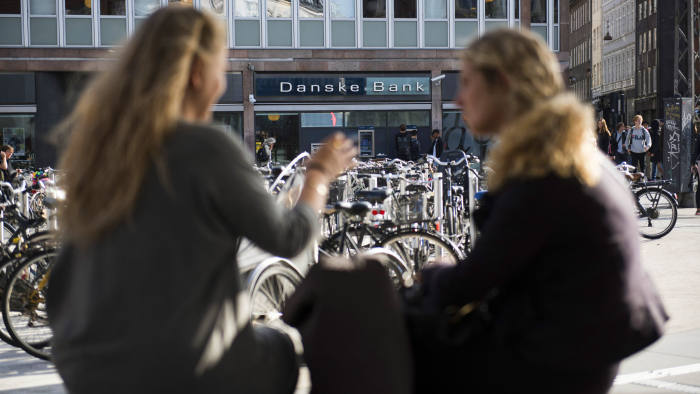 Pedestrians converse near a bike parking space outside a Danske Bank A/S bank branch in central Copenhagen, Denmark, on Wednesday, Sept. 19, 2018. Danske Bank A/SChief Executive OfficerThomas Borgen will step down amid allegations his bank was at the center of a major European money laundering scandal with as much as $234 billion flowing through a tiny unit in Estonia. Photographer: Freya Ingrid Morales/Bloomberg
