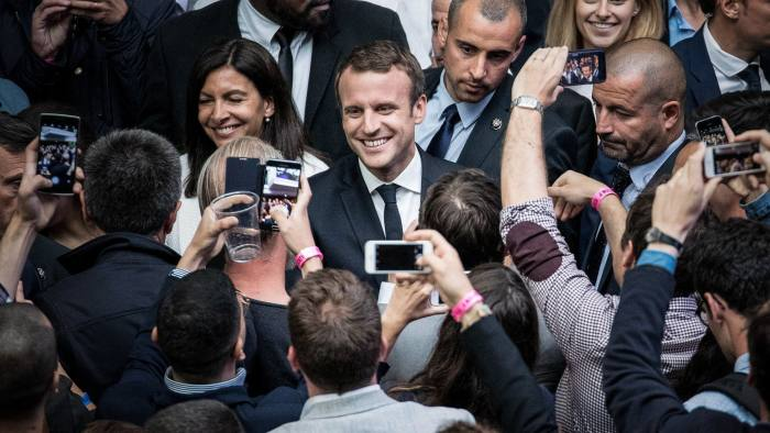 Emmanuel Macron, France's president, center, smiles for photographs during the Station F startup campus launch party in Paris, France, on Thursday, June 29, 2017. One of France's richest people, Niel spent 250 million euros ($268 million) to transform a former freight station into an incubator area, with some 3,000 desks for rent and numerous hangout areas. Photographer: Christophe Morin/Bloomberg