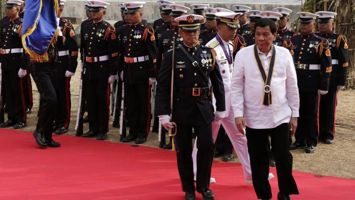 epa06755785 Filipino President Rodrigo Duterte (R) reviews honor guards during the 120th Philippine navy anniversary celebration in Manila, Philippines, 22 May 2018. Duterte in his speach said he wants to take on a stronger stance in the South China Sea dispute but this would come at a great cost. According to news reports, China recently deployed bomber planes in one of the disputed Spratly Islands. EPA/FRANCIS R. MALASIG