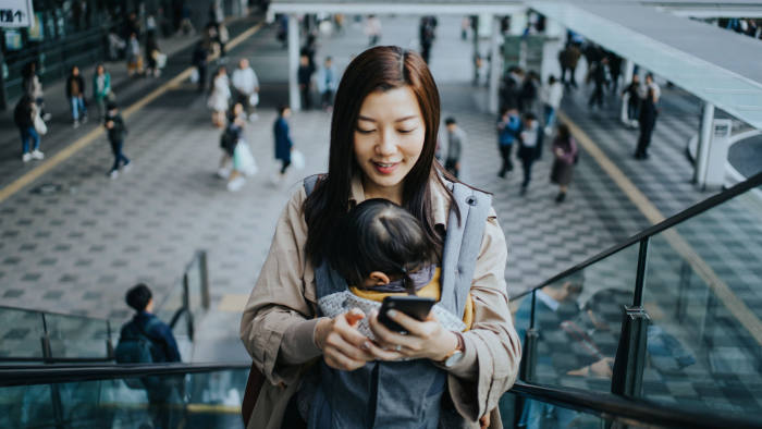 Young Asian mother with little daughter using smartphone while riding on escalator in downtown city, with busy commuters in the background