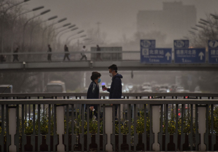 Pedestrians wear masks to protect themselves from unusually high levels of dust as they walk on an overpass during in Beijing on March 28, 2018. / AFP PHOTO / WANG ZHAO (Photo credit should read WANG ZHAO/AFP/Getty Images)