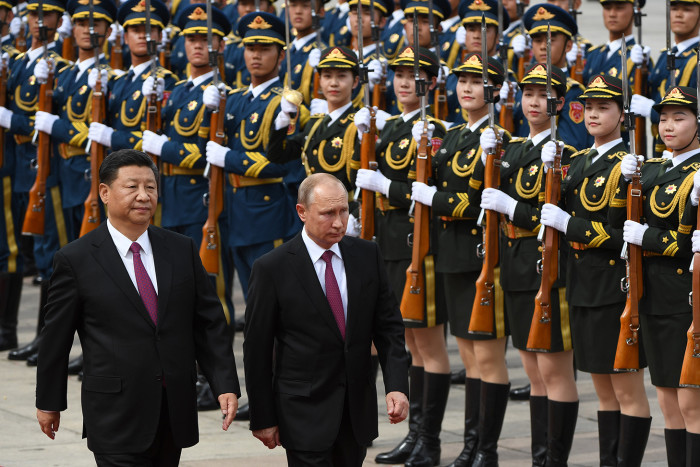 TOPSHOT - Russia's President Vladimir Putin (C) reviews a military honour guard with Chinese President Xi Jinping (L) during a welcoming ceremony outside the Great Hall of the People in Beijing on June 8, 2018. - Putin arrived on June 8 for a state visit to China and will attend the Shanghai Cooperation Organisation Leaders Summit in the eastern port city of Qingdao on June 9-10. (Photo by Greg BAKER / POOL / AFP) (Photo credit should read GREG BAKER/AFP/Getty Images)