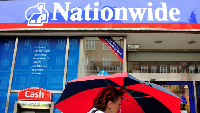 FILE PHOTO: A woman passes a branch of the Nationwide Building Society in London May 27, 2009. REUTERS/Toby Melville/File Photo