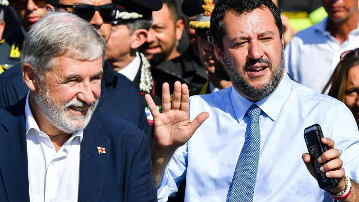 Mandatory Credit: Photo by SIMONE ARVEDA/EPA-EFE/Shutterstock (10323450al) Italian Deputy Premier and Interior Minister Matteo Salvini (R) speaks with journalists next to Genoa City's mayor Marco Bucci following the Morandi highway bridge's pillars demolition, in Genoa, northern Italy, 28 June 2019. Thousands of people were evacuated ahead of the demolition works, which started on the day. Experts have blown up the remains of the bridge which partially collapsed on 14 August 2018 killing 43 people. A new viaduct replacing the Morandi bridge is expected to be completed by 2020. Morandi Bridge collapse: demolition works, Genoa, Italy - 28 Jun 2019