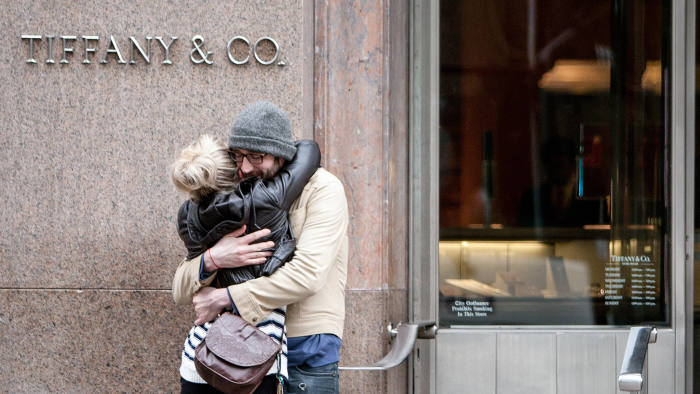 A couple embraces in front of a Tiffany & Co. store in New York, U.S., on Thursday, March 15, 2012. Tiffany & Co., the world's second-largest luxury jewelry retailer, is expected to release earnings next week. Photographer: Scott Eells/Bloomberg