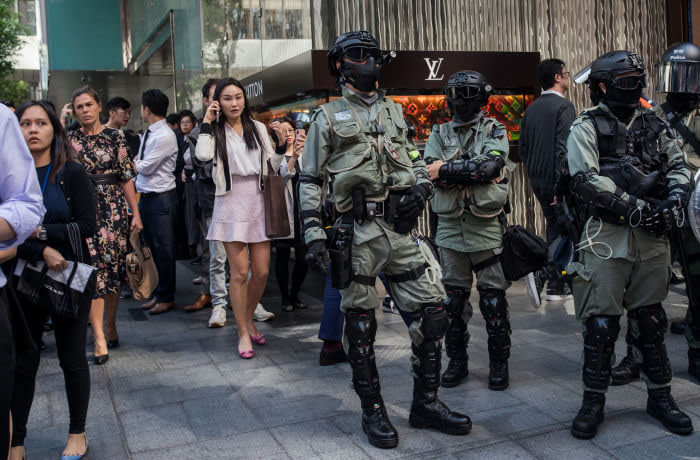 Riot police and office workers stand near a Louis Vuitton luxury good store during a protest in the Central district of Hong Kong, China, on Monday, Nov. 11, 2019. A Hong Kong protester was in critical condition after being shot by a police officer, as the financial hub reeled from citywide efforts to disrupt the work week amid worsening political unrest. Photographer: Nicole Tung/Bloomberg