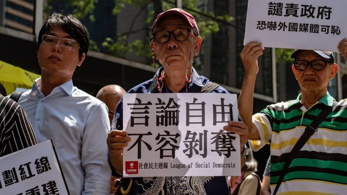 """A demonstrator (C) holds a placard that reads """"freedom of the press, not allowed to be deprived"""" during a protest after Hong Kong immigration authorities declined a visa renewal for senior Financial Times journalist Victor Mallet, outside the immigration department building in Hong Kong on October 6, 2018. - Hong Kong's decision to effectively blacklist a senior Financial Times journalist required an """"urgent explanation"""", the UK said October 6, as foreign governments sounded the alarm over eroding freedoms in the former British colony. (Photo by Philip FONG / AFP)PHILIP FONG/AFP/Getty Images"""