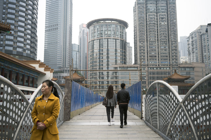 CHONGQING, CHINA - 3 APRIL 2019. People walk among buildings in central Chongqing. (Giulia Marchi for The Financial Times) pfeatures