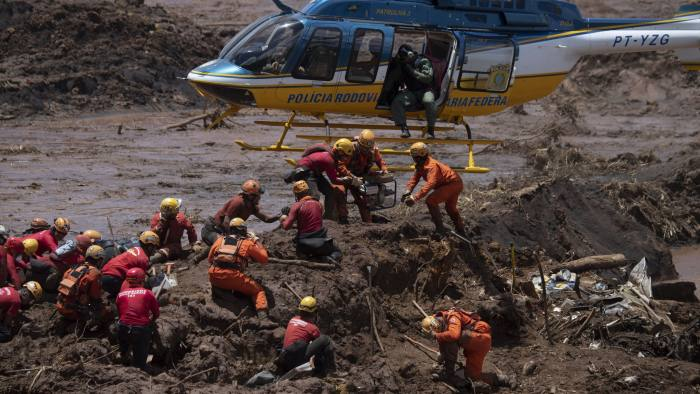 TOPSHOT - Firefighters receive equipment to open a vehicle found in the mud as they search for victims of Friday's dam collapse at an iron-ore mine belonging to Brazil's giant mining company Vale near the town of Brumadinho, state of Minas Gerais, southeastern Brazil, on January 28, 2019. - The search for survivors intensified on Monday, on its fourth day, with the support of an Israeli contingent, after communities were devastated by a dam collapse that killed at least 60 people -- with hopes fading for 292 still missing. A barrier at the site burst on Friday, spewing millions of tons of treacherous sludge and engulfing buildings, vehicles and roads. (Photo by Mauro PIMENTEL / AFP)        (Photo credit should read MAURO PIMENTEL/AFP/Getty Images)