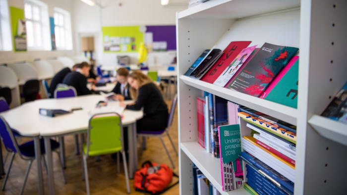 KHKJ2A Secondary Education in the UK: University propectuses on a bookshelf in a sixth form common room
