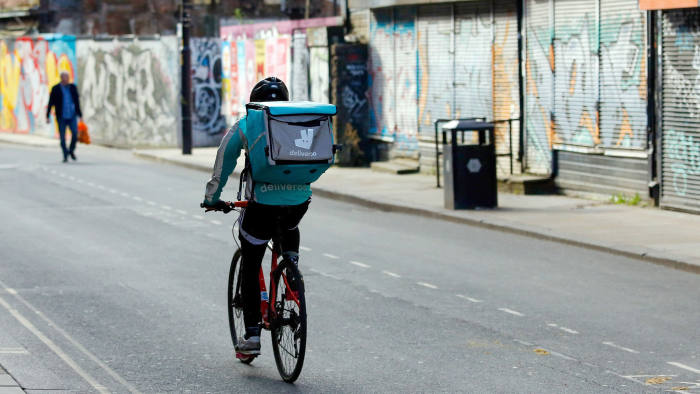 A food delivery courier for Deliveroo, operated by Roofoods Ltd., cycles in Manchester, U.K., on Wednesday, April 8, 2020. The U.K. has been racing to protect businesses and workers from the effects of the pandemic and the restrictions imposed to combat it. Photographer: Paul Thomas/Bloomberg