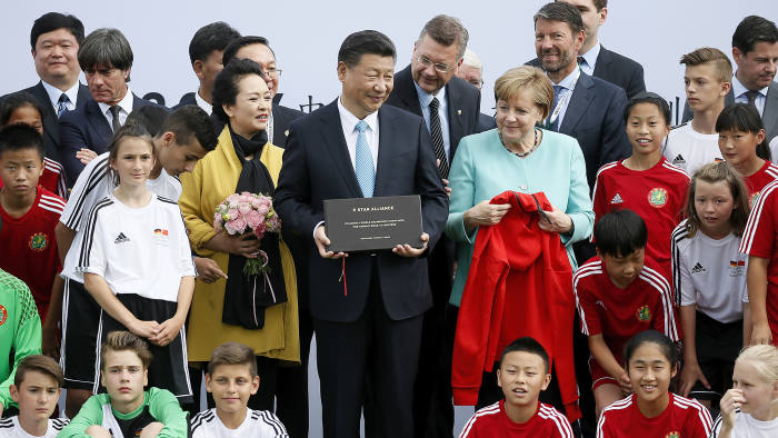 epa06067969 Chinese President Xi Jinping and his wife Peng Liyuan and German Chancellor Angela Merkel get gifts by U12 children of Germany and China during their visit in Olympic Park in Berlin, Germany, 05 July 2017. Chancellor Angela Merkel and the Chinese President of the People's Republic of China, Xi Jinping, will be informing about the current status of cooperation in the field of football at the Olympic Park in Berlin. EPA/RONALD WITTEK / POOL