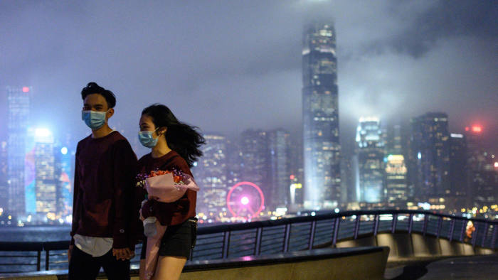 A couple wears face masks as a preventative measure against the COVID-19 coronavirus, as they walk along the promenade in Tsim Sha Tsui of Hong Kong on February 14, 2020. - The death toll from China's virus epidemic neared 1,400 on Friday with six medical workers among the victims, underscoring the country's struggle to contain a deepening health crisis. (Photo by Philip FONG / AFP) (Photo by PHILIP FONG/AFP via Getty Images)