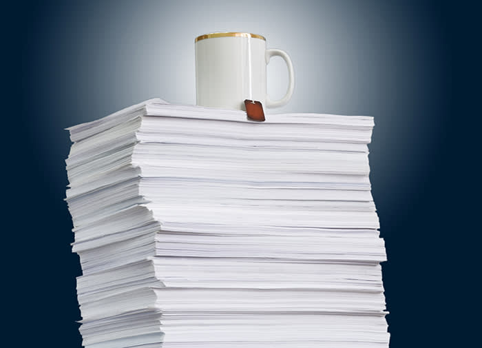high paper stack and a cup of tea