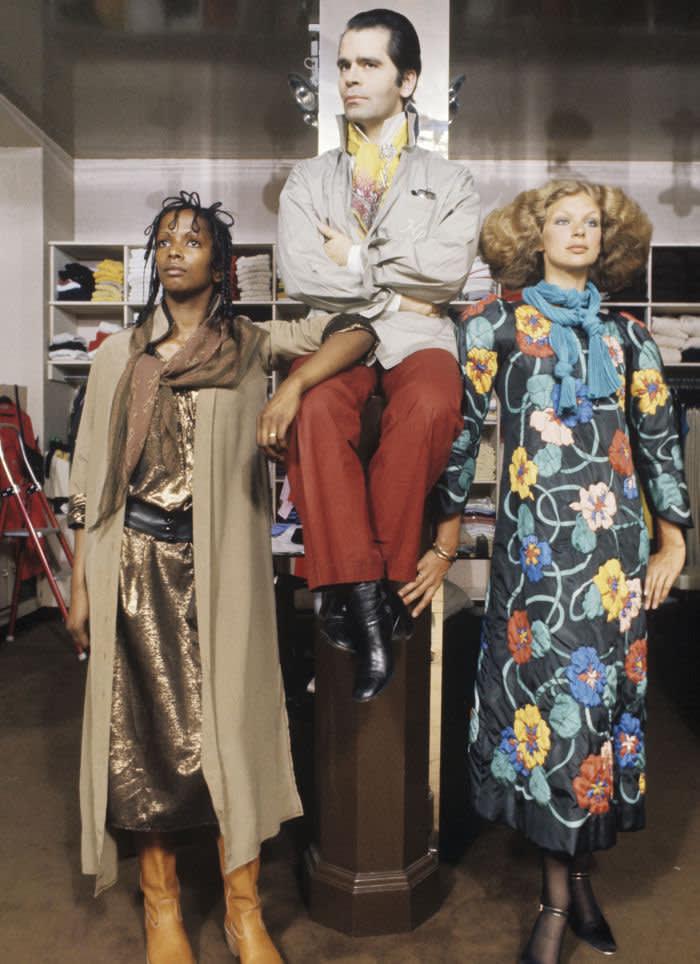 Paris, France, juillet 1976 --- Karl LAGERFELD, styliste de Chloé, la griffe la plus chère du prêt-à-porter français, présente les modèles d'hiver. Le styliste posant dans la boutique avec deux mannequins portant ses créations. (Photo by SAUER Jean-Claude/Paris Match via Getty Images)