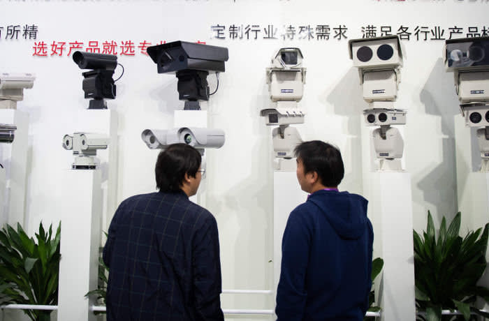 Visitors look at AI (Artificial Inteligence) security cameras using facial recognition technology at the 14th China International Exhibition on Public Safety and Security at the China International Exhibition Center in Beijing on October 24, 2018. (Photo by NICOLAS ASFOURI / AFP) (Photo credit should read NICOLAS ASFOURI/AFP via Getty Images)