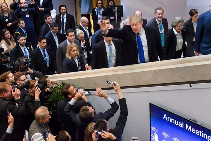 TOPSHOT - US President Donald Trump (C) waves upon his arrival at the Economic Forum (WEF) annual meeting on January 25, 2018 in Davos, eastern Switzerland. The world's political and business elite headed on January 25 into a compelling encounter with President Donald Trump as the United States bids to carve out a competitive edge in trade, taxes and currency rates. / AFP PHOTO / Fabrice COFFRINIFABRICE COFFRINI/AFP/Getty Images