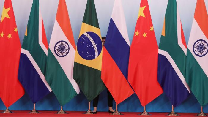A member of staff stands behind national flags of Brazil, Russia, China, South Africa and India to tidy the flags ahead a group photo during the BRICS Summit at the Xiamen International Conference and Exhibition Center in Xiamen, southeastern China's Fujian Province on September 4, 2017.  Xi opened the annual summit of BRICS leaders that already has been upstaged by North Korea's latest nuclear weapons provocation. / AFP PHOTO / POOL / WU HONG        (Photo credit should read WU HONG/AFP/Getty Images)