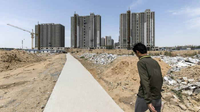 A worker walks towards residential buildings under construction in Qingdao, China, on Tuesday, May 8, 2018. China is scheduled to release new home price figures on May 16. Photographer: Qilai Shen/Bloomberg