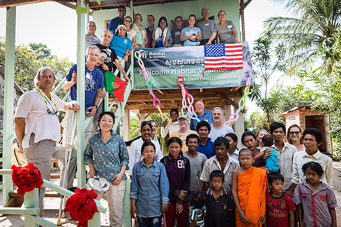 Yot Sat and Phit Pik's family with Habitat volunteers and Yuan Yang, at the foot of the stairs, outside their new house