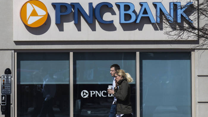 """Two people walk past a PNC bank office in Arlington, Virginia on March 18, 2015. The Federal Reserve dropped its pledge to remain """"patient"""" on raising interest rates, signaling a possible midyear fed funds rate hike after over six years at the zero level. AFP PHOTO/ ANDREW CABALLERO-REYNOLDS (Photo credit should read Andrew Caballero-Reynolds/AFP/Getty Images)"""