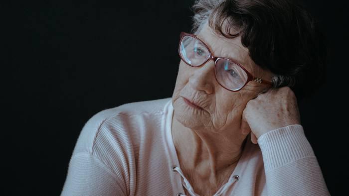 Sad senior woman with glasses sitting alone against black background