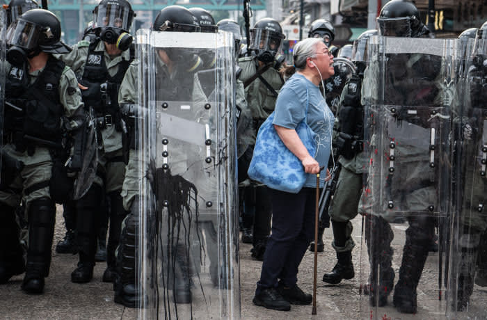 """***2019 News Images Of The Year*** - HONG KONG, CHINA - JULY 27: A woman shouts at police officers as they advance towards protesters in the district of Yuen Long on July 27, 2019 in Hong Kong, China. Pro-democracy protesters have continued weekly rallies on the streets of Hong Kong against a controversial extradition bill since 9 June as the city plunged into crisis after waves of demonstrations and several violent clashes. Hong Kong's Chief Executive Carrie Lam apologized for introducing the bill and recently declared it """"dead"""", however protesters have continued to draw large crowds with demands for Lam's resignation and completely withdraw the bill. (Photo by Laurel Chor/Getty Images)"""