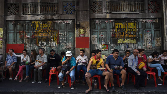 TOPSHOT - People sit and eat a meal on a side-walk in Bangkok's Chinatown on February 4, 2016. AFP PHOTO / Christophe ARCHAMBAULT / AFP / CHRISTOPHE ARCHAMBAULT (Photo credit should read CHRISTOPHE ARCHAMBAULT/AFP via Getty Images)