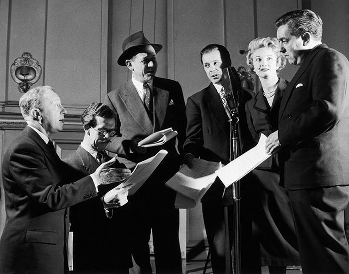 Cast members at a recording for the first series of the BBC radio comedy show, 'Hancock's Half Hour', London, 1954. From third left: (left to right): Sid James (1913 - 1976), Bill Kerr, Moira Lister and Tony Hancock (1924 - 1968). (Photo by Paul Popper/Popperfoto/Getty Images)