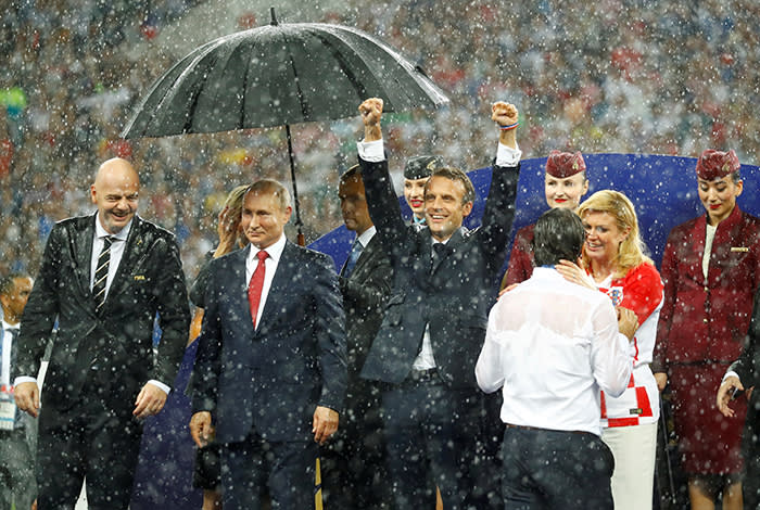"Soccer Football - World Cup - Final - France v Croatia - Luzhniki Stadium, Moscow, Russia - July 15, 2018 President of Croatia Kolinda Grabar-Kitarovic consoles Croatia coach Zlatko Dalic as FIFA president Gianni Infantino, President of Russia Vladimir Putin and President of France Emmanuel Macron look on during the presentation. Kai Pfaffenbach: ""Usually a football World Cup is all about the action, goals and emotions on the pitch. This World Cup's final had a lot of that too, but despite the 4-2 result my favourite picture is this. As soon as the victory ceremony started, a heavy downpour began. A helper had an umbrella for Russia President Vladimir Putin quickly on hand, while his counterparts from France and Croatia enjoyed a little shower along with FIFA President Gianni Infantino. France President Emmanuel Macron didn't seem to care and enjoyed himself - and his team's victory - while Croatia President Kolinda Grabar-Kitarovic comforted her team's coach."" REUTERS/Kai Pfaffenbach/File Photo SEARCH ""PHOTOGRAPHERS BEST"" FOR THIS STORY. SEARCH ""WIDER IMAGE"" FOR ALL STORIES. TPX IMAGES OF THE DAY."