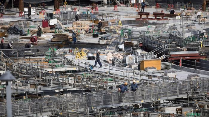 Workers perform their duties at the construction site for the National Stadium, venue for the upcoming Tokyo 2020 Olympic Games, in Tokyo on July 21, 2017. The suicide of a 23-year-old worker on Tokyo's Olympic stadium was due to overwork, his family said on July 21, as Japan races to finish building venues for the 2020 Games. / AFP PHOTO / Behrouz MEHRI (Photo credit should read BEHROUZ MEHRI/AFP/Getty Images)