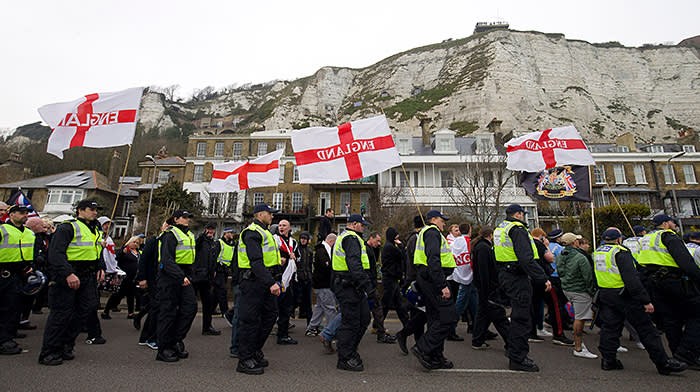Police walk beside groups of far right protesters marching through Dover, southern England, on April 2, 2016. / AFP / JUSTIN TALLIS (Photo credit should read JUSTIN TALLIS/AFP/Getty Images)