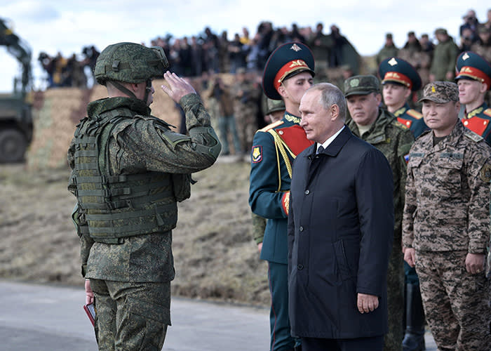 Russian President Vladimir Putin, right, awards a Russian serviceman as he attends a military exercises on training ground